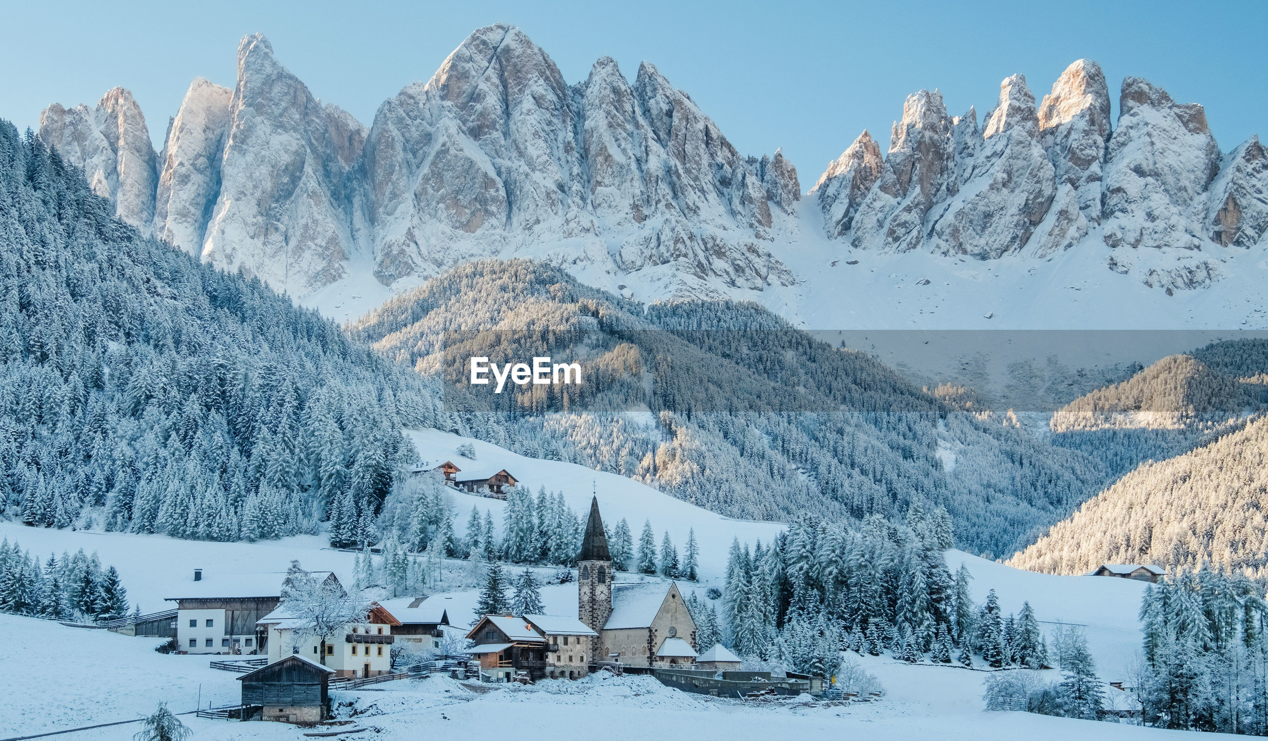 The small village val di funes covered in snow, with dolomites mountains, south tyrol, italy.