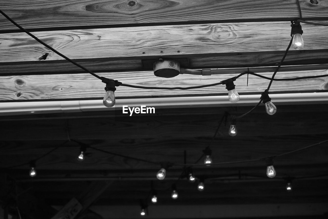 low angle view, hanging, ceiling, lighting equipment, no people, indoors, illuminated, architecture, day, roof, light bulb, electricity, built structure, cable, decoration, textile, technology, wood - material, pattern, light, roof beam, stage