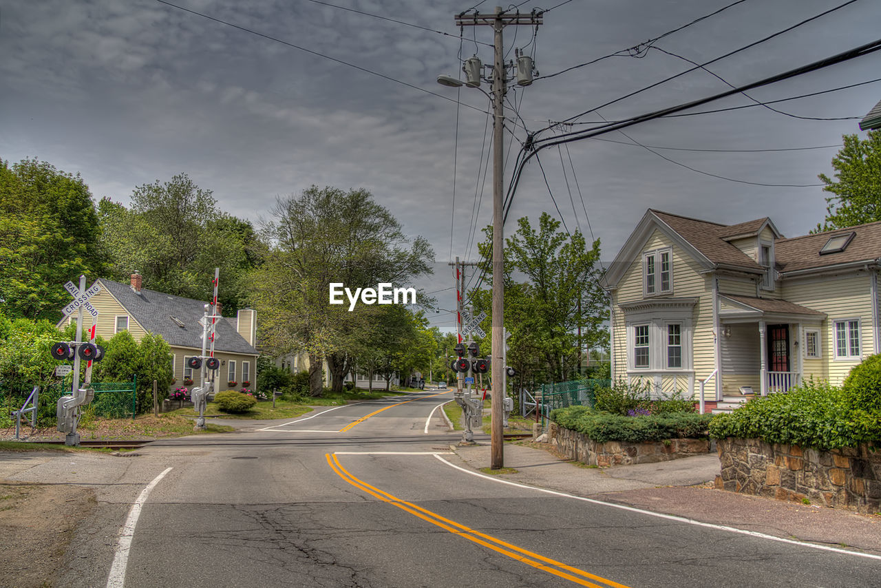 built structure, architecture, building exterior, cable, tree, house, day, outdoors, power supply, road, electricity pylon, transportation, the way forward, sky, no people, electricity, residential building