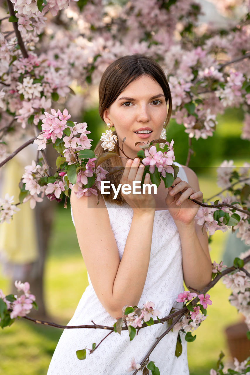 PORTRAIT OF BEAUTIFUL WOMAN WITH PINK FLOWER AGAINST PLANTS