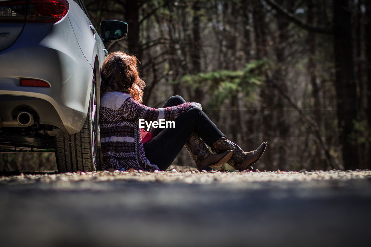 Woman Sitting Against Car