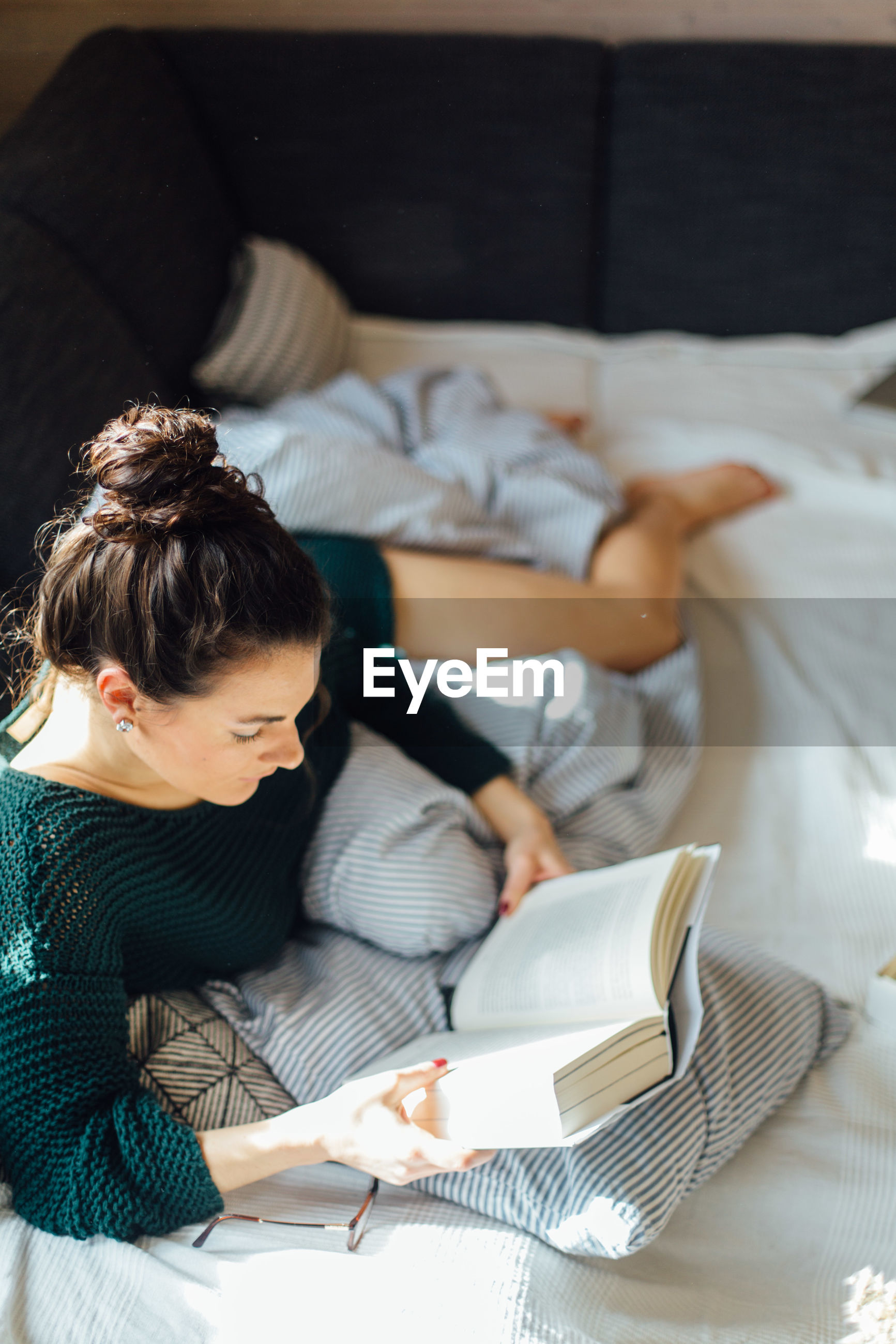 High angle view of young woman reading book while lying on bed at home