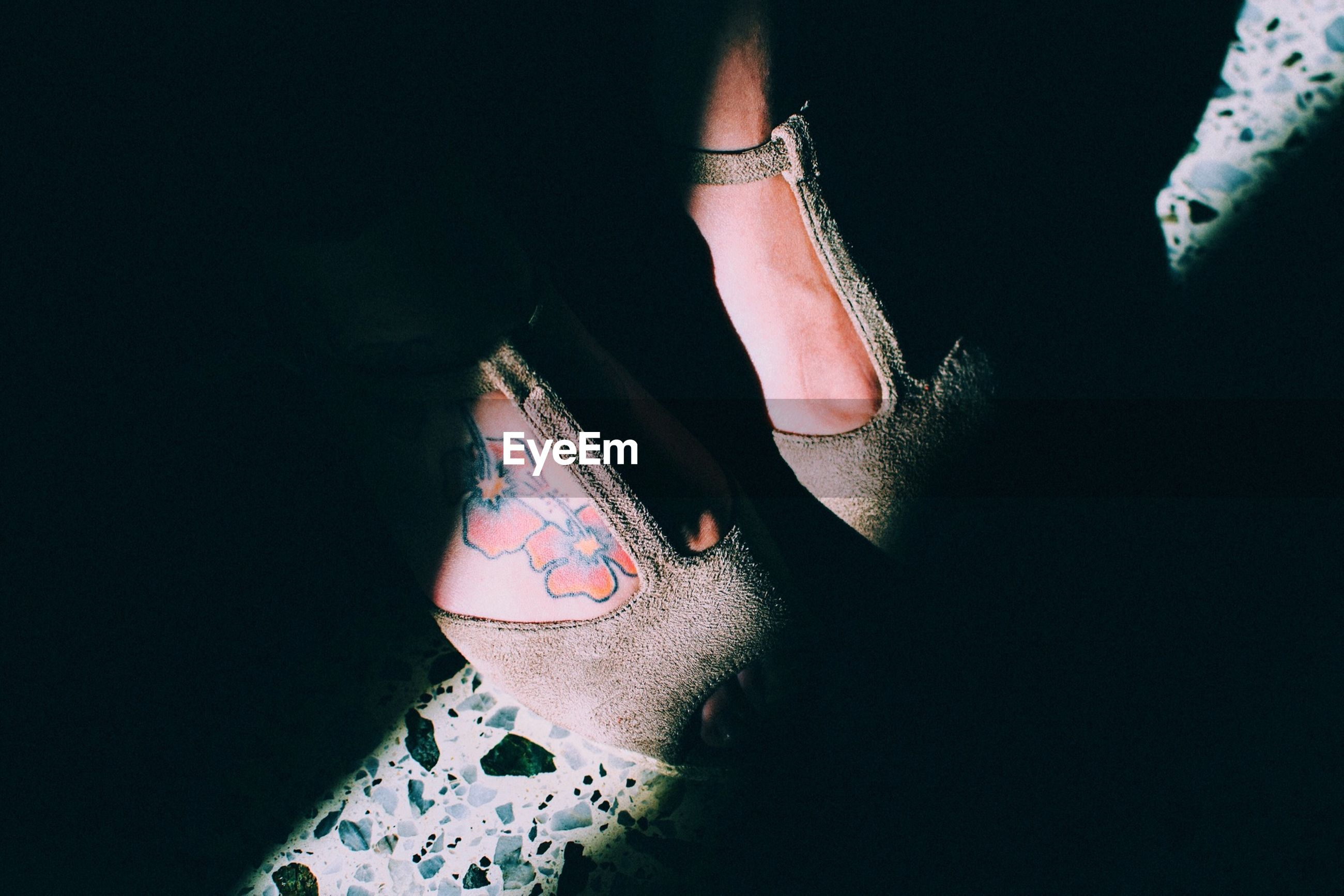 Low section of woman wearing shoes with flower tattoo