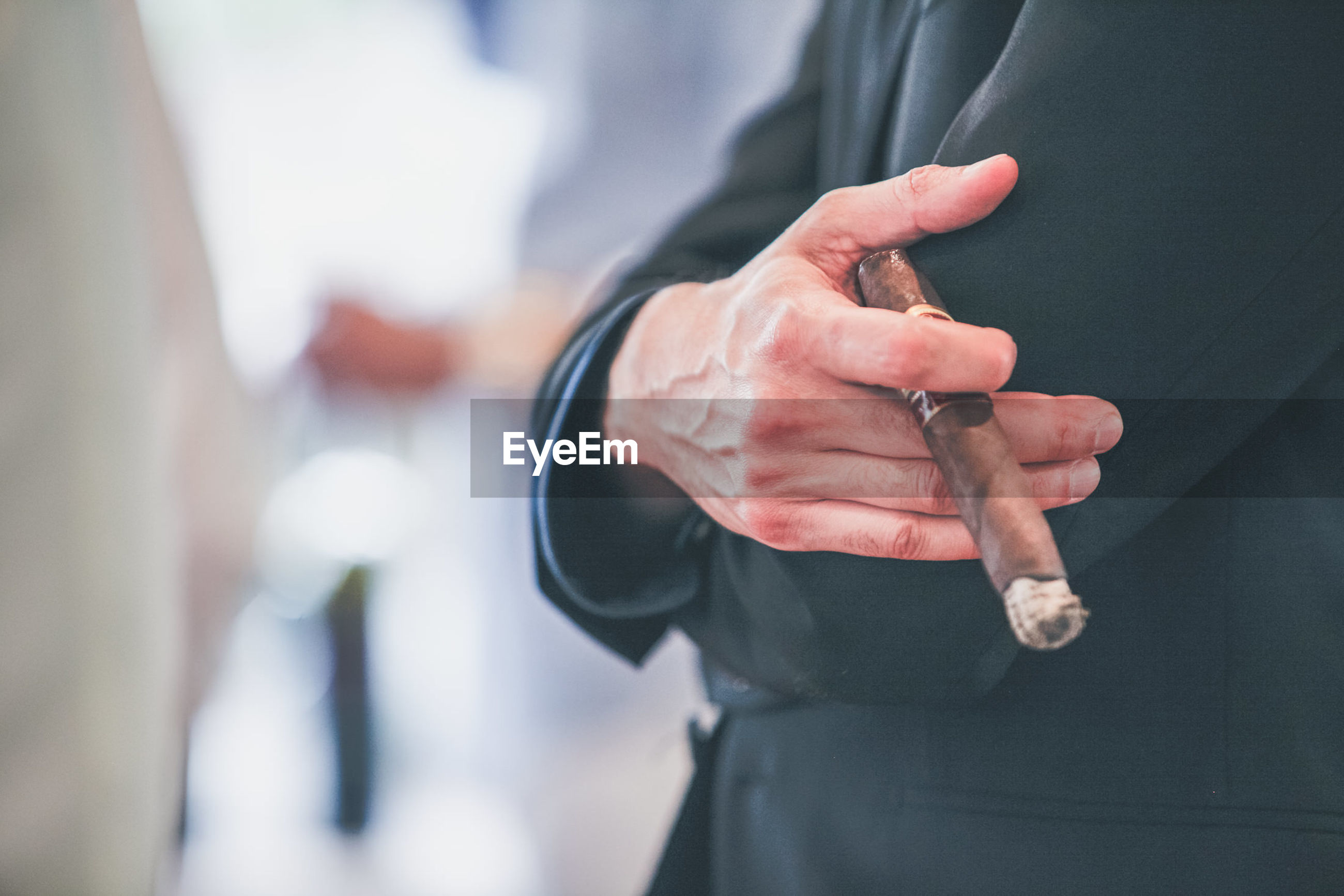 Low section of man holding cigar