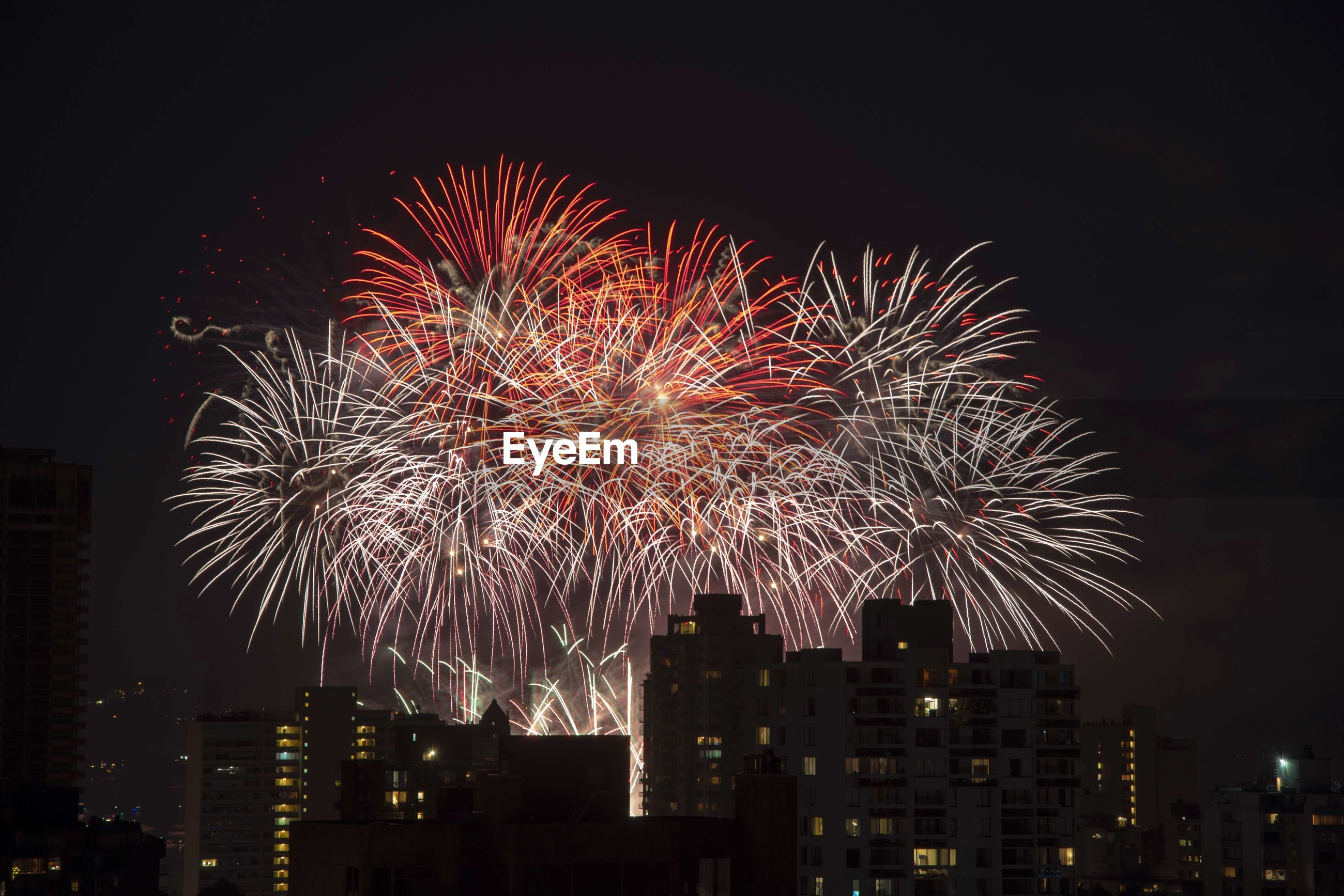 Firework display over cityscape at night