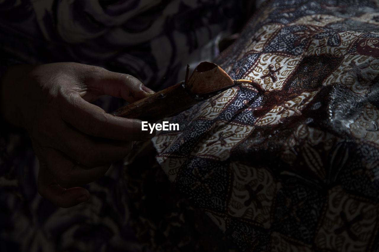 Cropped hand of craftsperson making batik at workshop
