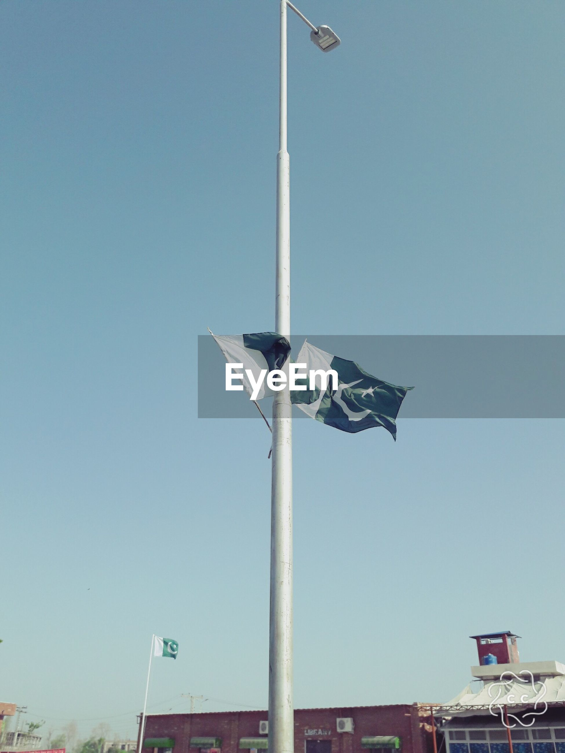 flag, clear sky, low angle view, day, outdoors, sky, blue, no people, road sign
