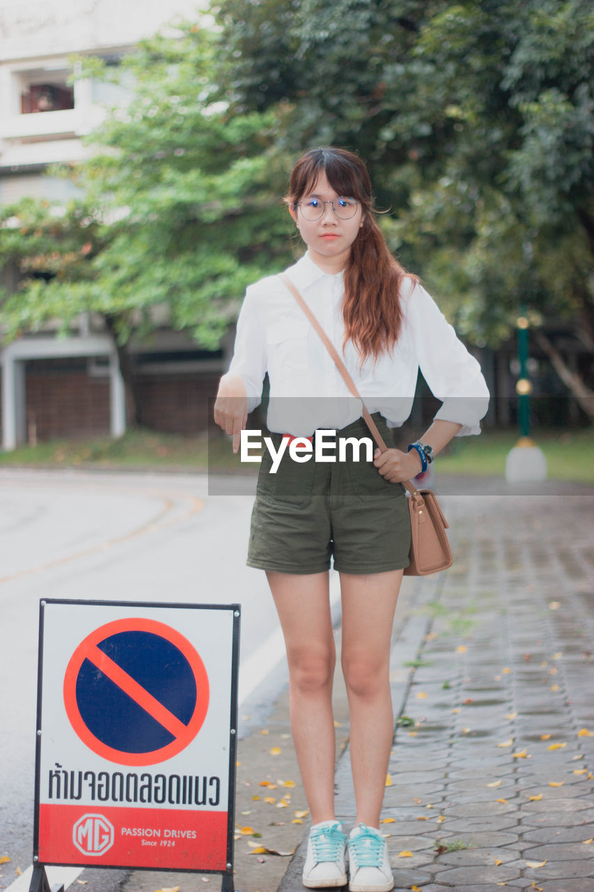 one person, real people, lifestyles, standing, front view, focus on foreground, leisure activity, women, young adult, fashion, young women, day, casual clothing, portrait, brown hair, hairstyle, adult, beauty, beautiful woman, outdoors, shorts