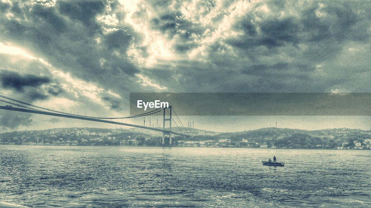 suspension bridge, bridge - man made structure, sky, connection, transportation, water, cloud - sky, architecture, outdoors, weather, travel destinations, day, river, waterfront, nature, travel, mountain, no people, built structure, tranquility, scenics, beauty in nature, city