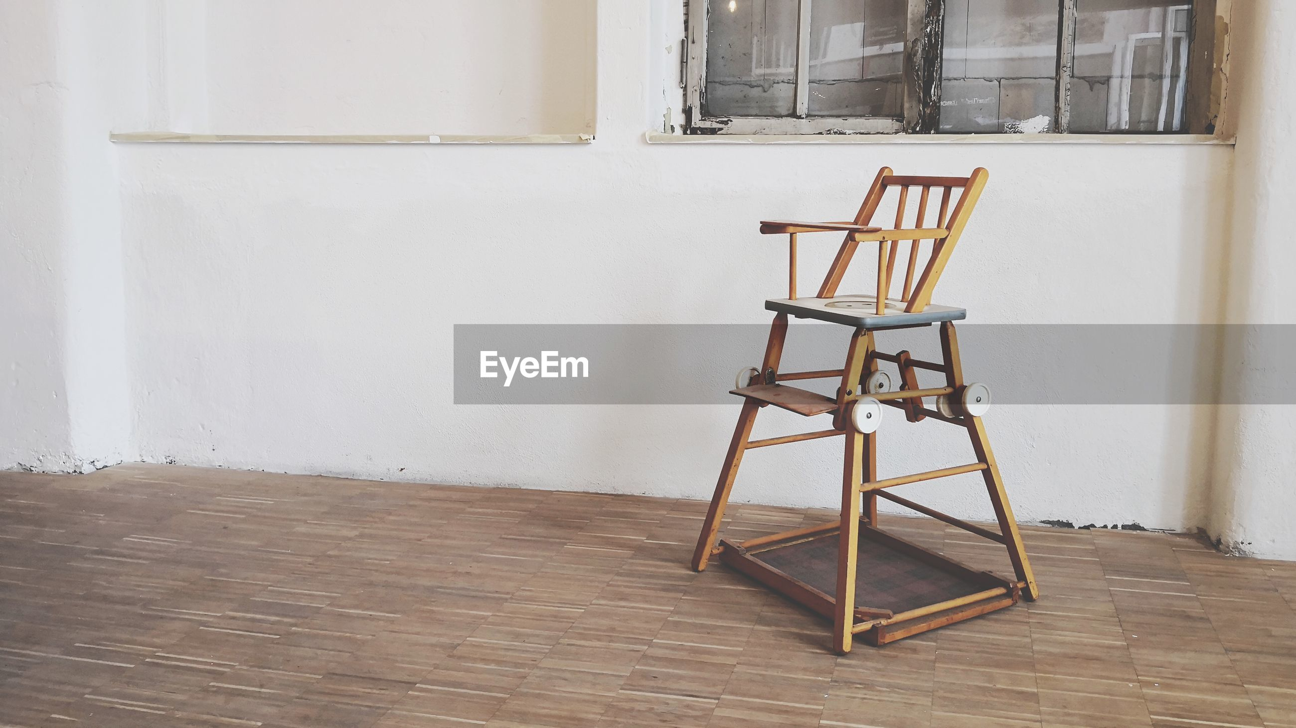 EMPTY CHAIR BY TABLE AGAINST WALL