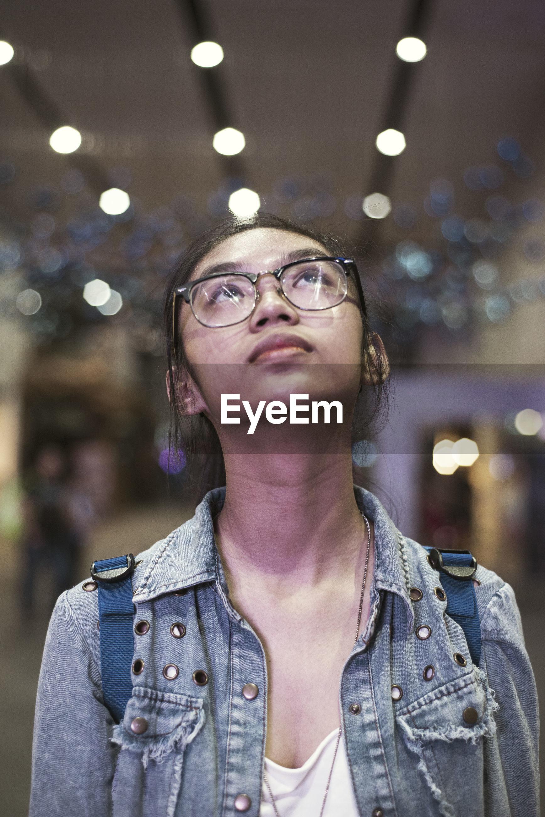 Close-up of teenage girl looking up against defocused lights