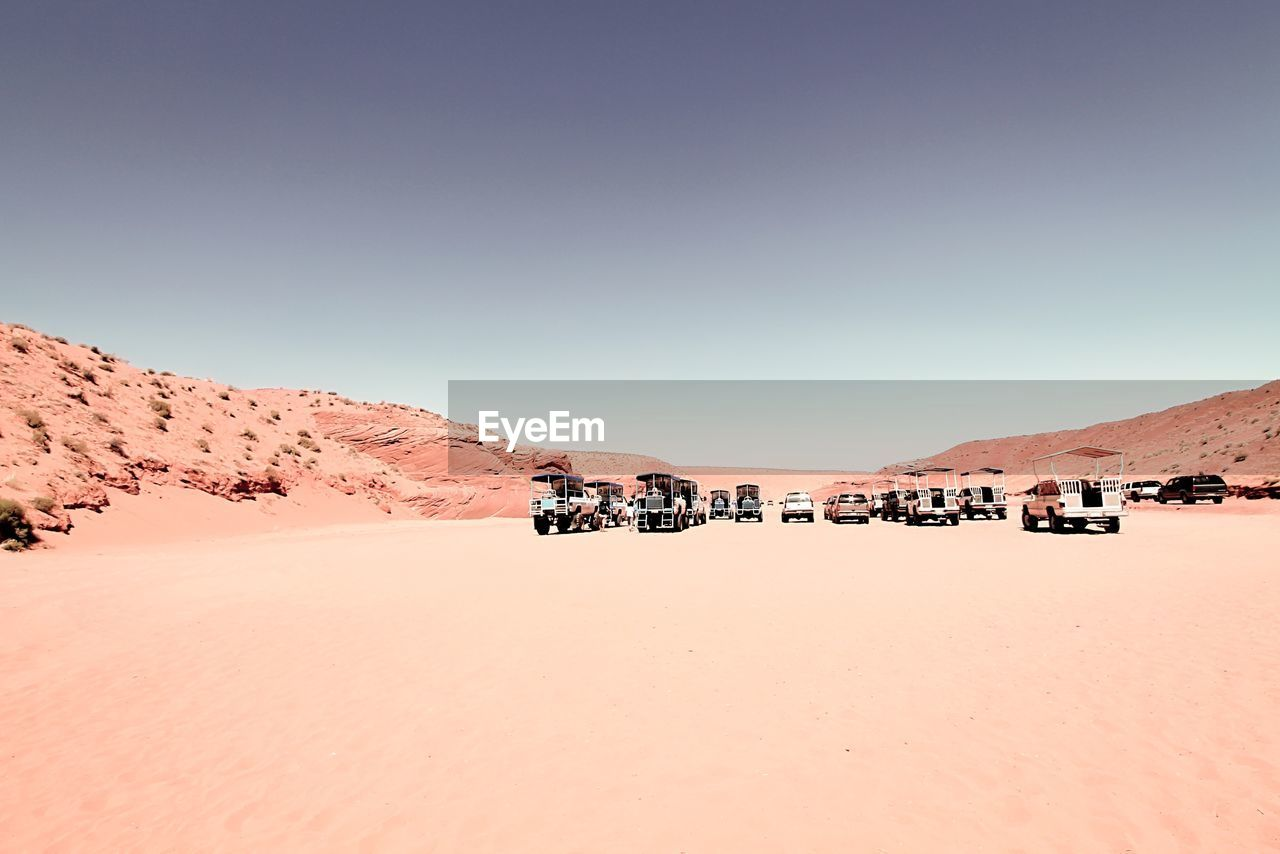 Vehicles Parked On Sand At Antelope Canyon