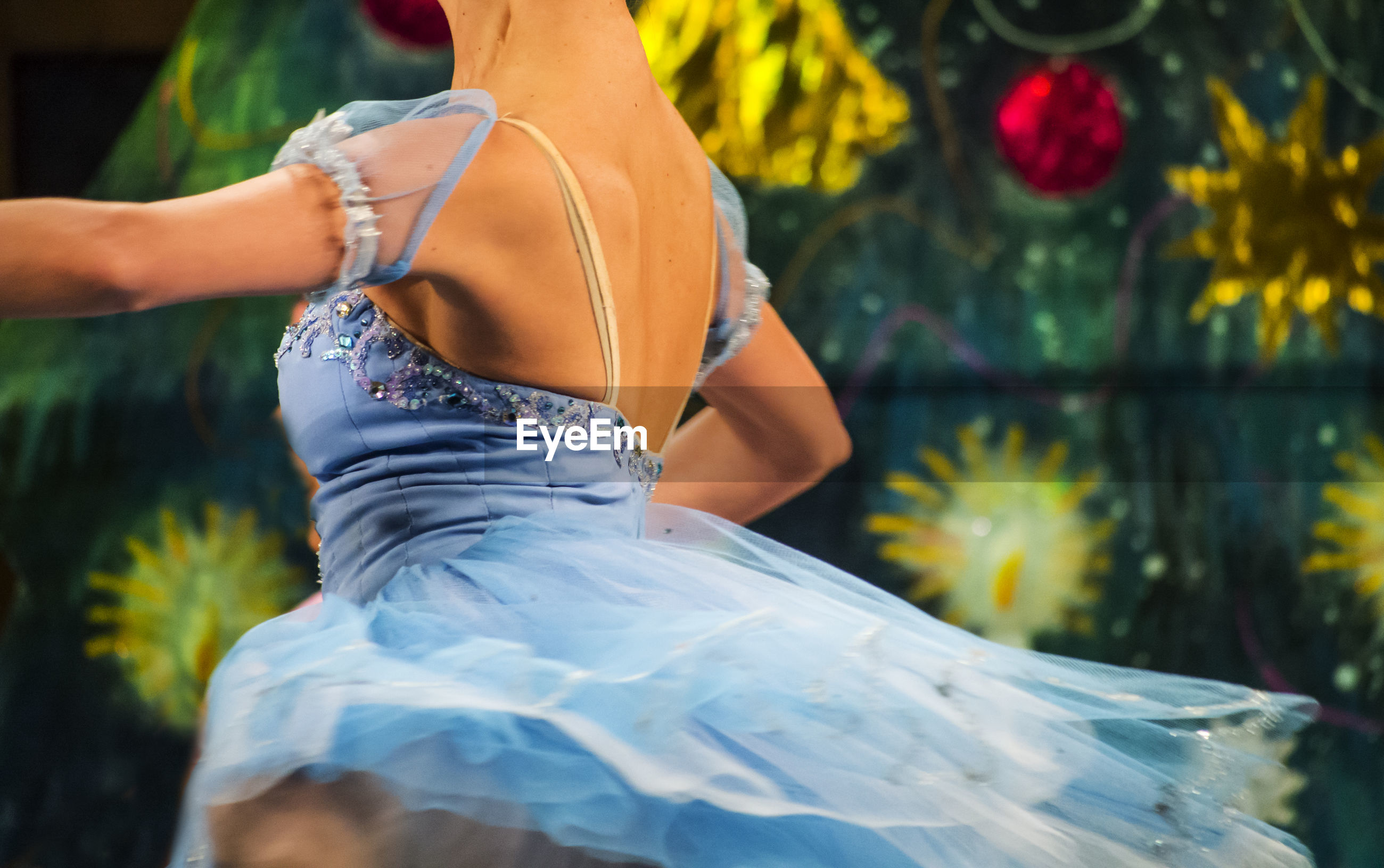 Midsection of ballerina dancing in blue dress