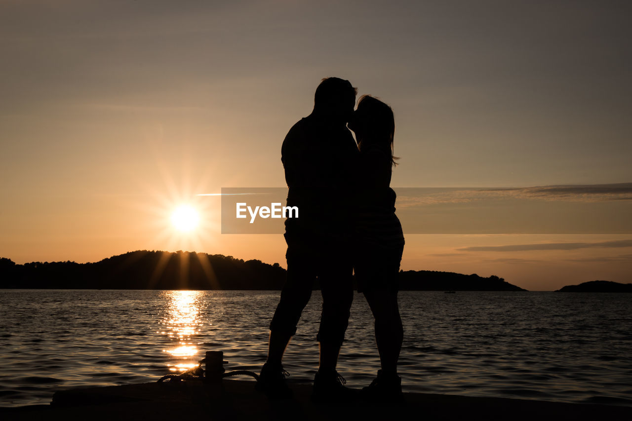 sunset, two people, silhouette, love, togetherness, romance, sun, nature, beauty in nature, orange color, bonding, men, sky, water, couple - relationship, real people, romantic, scenics, standing, sea, lifestyles, full length, outdoors, women, people