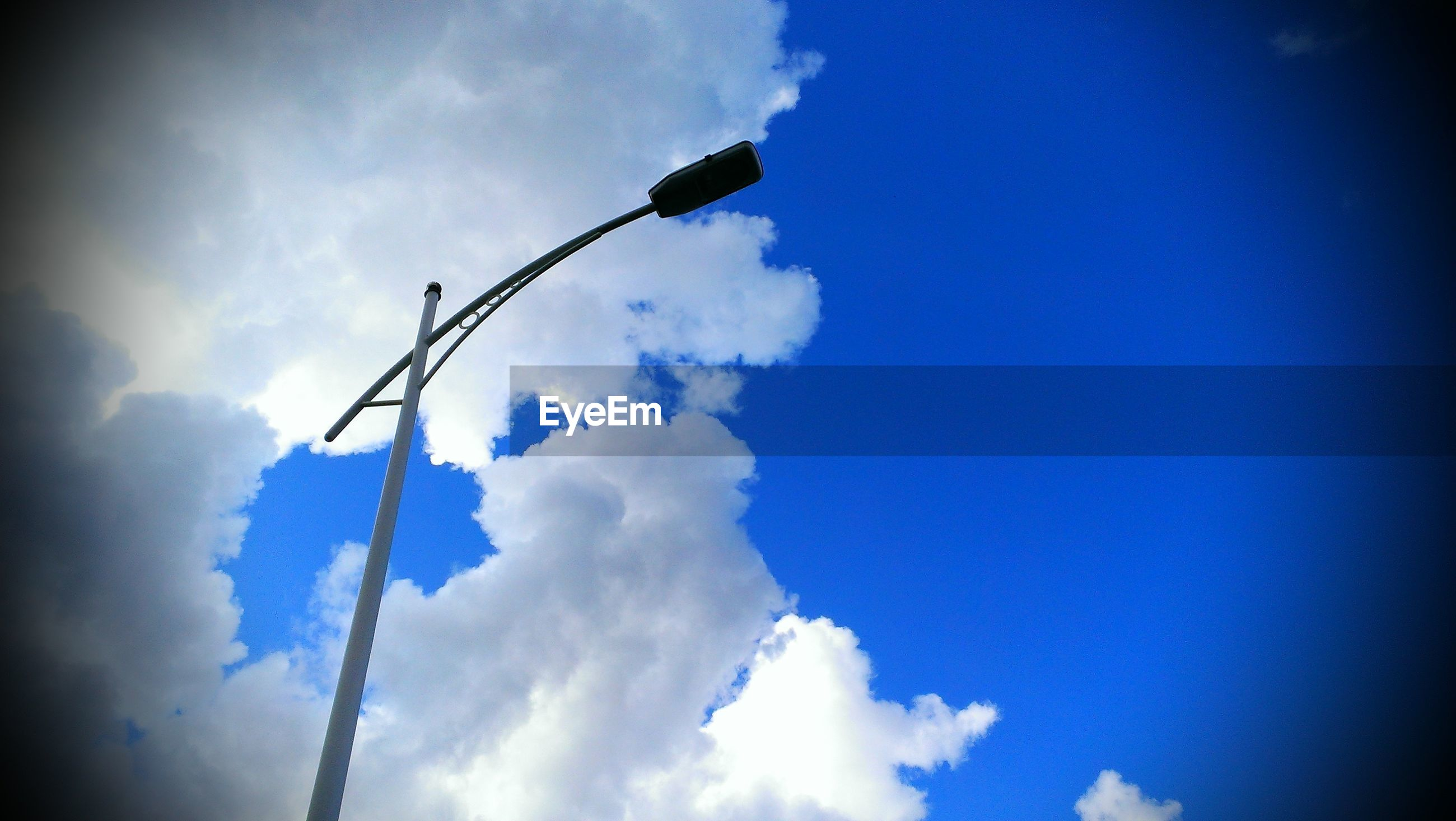 Low angle view of street light against white clouds and blue sky