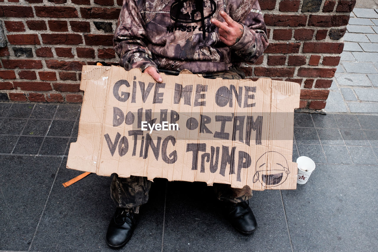 Low section of beggar with sign sitting by brick wall