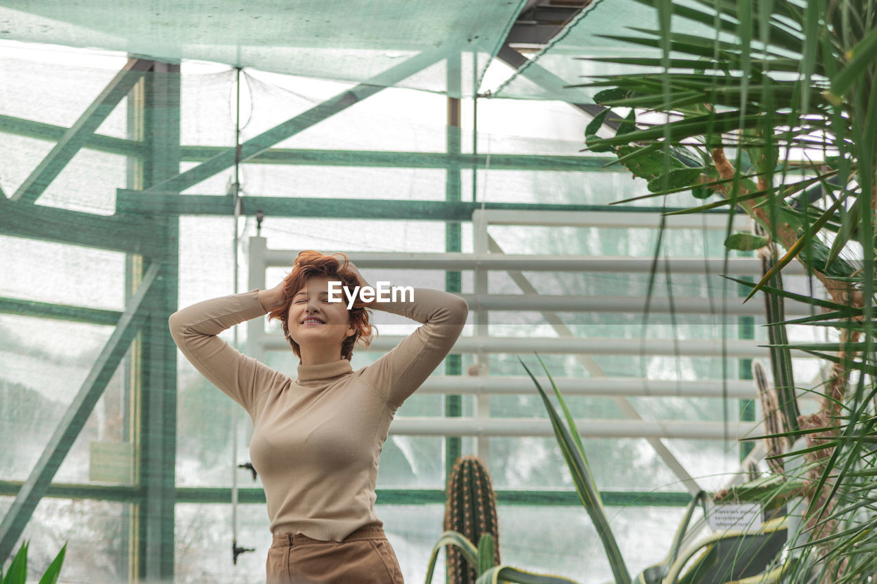 A beautiful plus size girl enjoying standing among the green plants of the greenhouse.