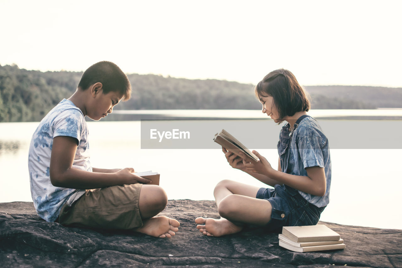 Siblings reading books while sitting at lakeshore