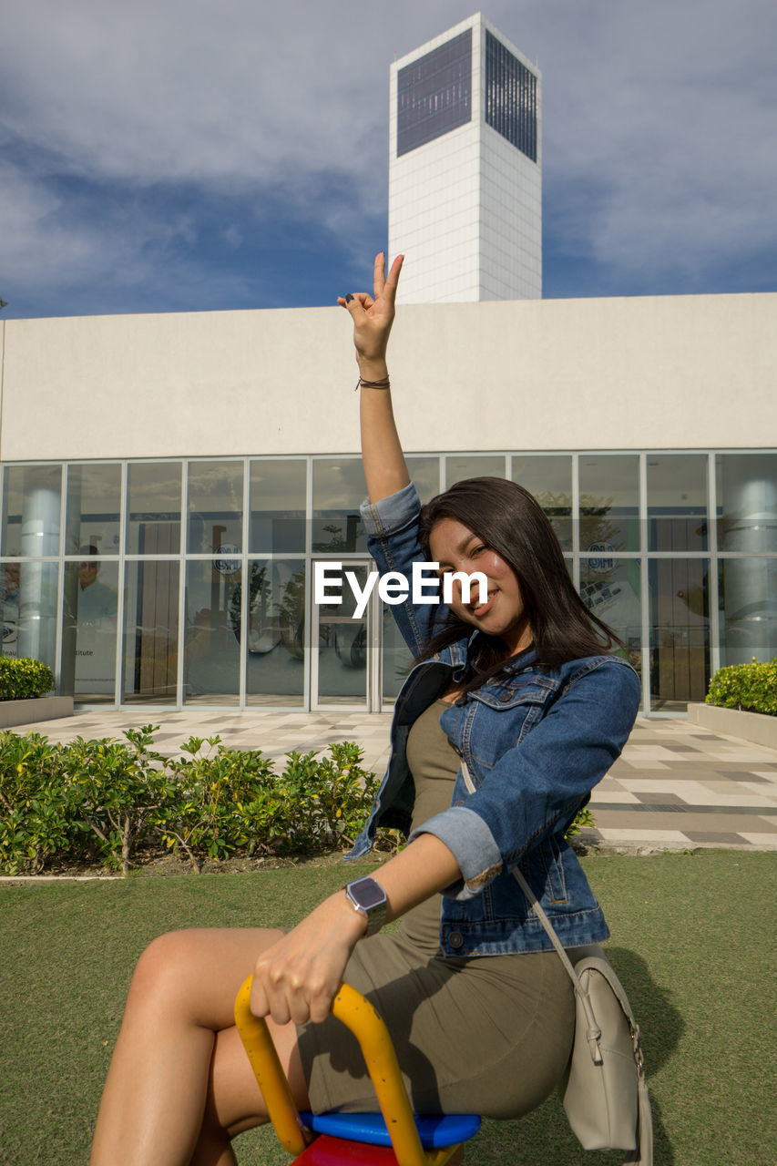 Woman gesturing peace sign sitting against building