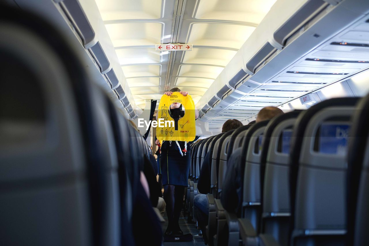 mode of transportation, public transportation, transportation, rail transportation, train, travel, vehicle interior, train - vehicle, vehicle seat, real people, airplane, air vehicle, men, seat, rear view, journey, people, group of people, indoors, lifestyles, airplane seat, subway train