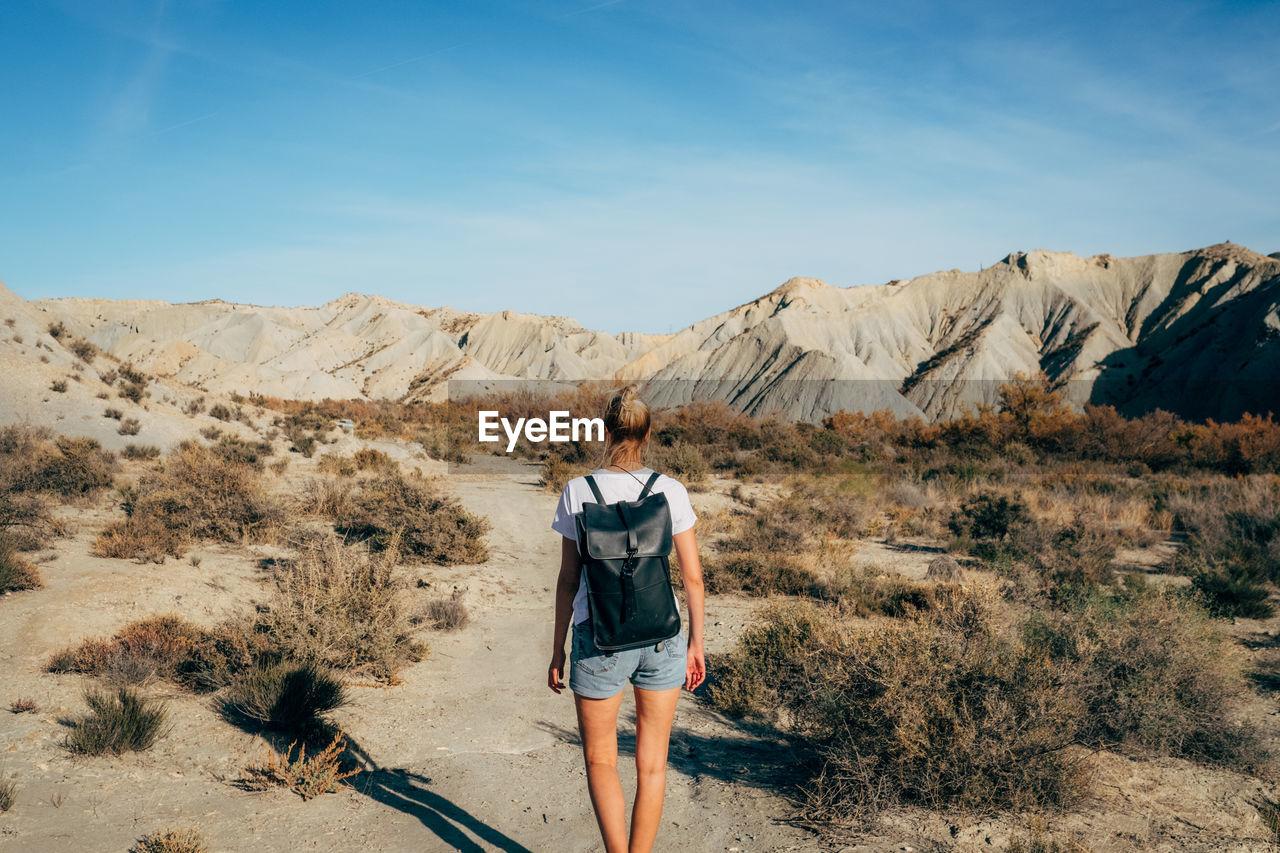 Rear view of woman walking on desert against sky