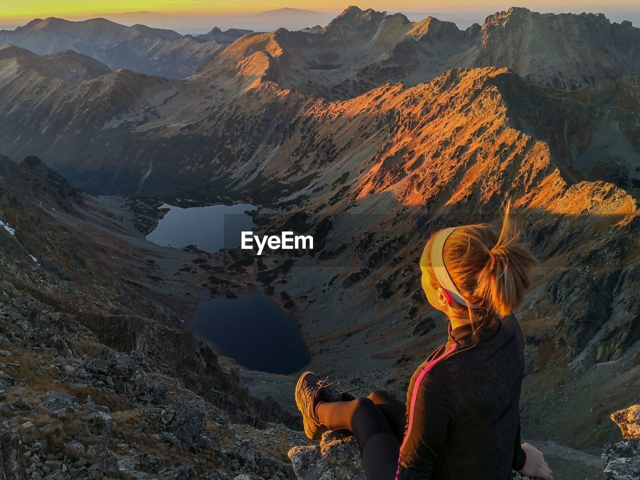 Rear view of woman sitting on cliff looking at mountain range