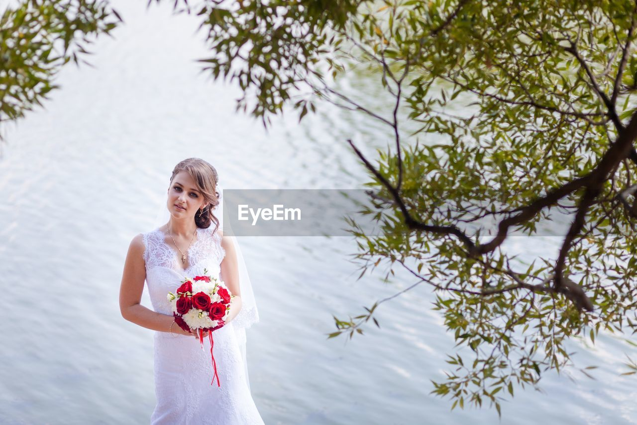 Portrait of bride standing against lake