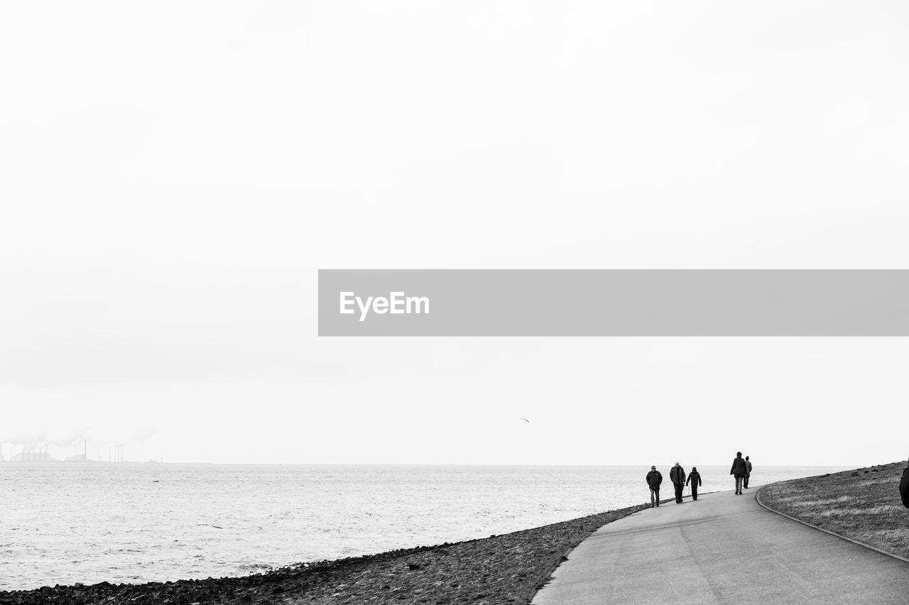 People Walking On Road By Sea Against Clear Sky