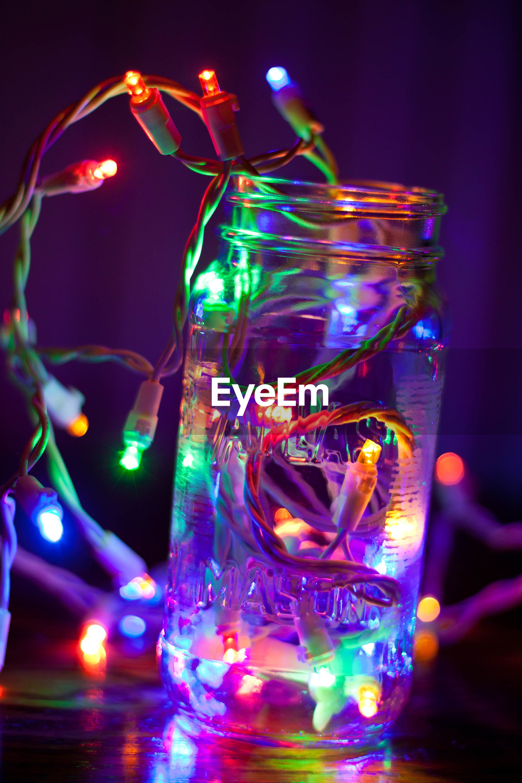Illuminated christmas lights in glass jar on table