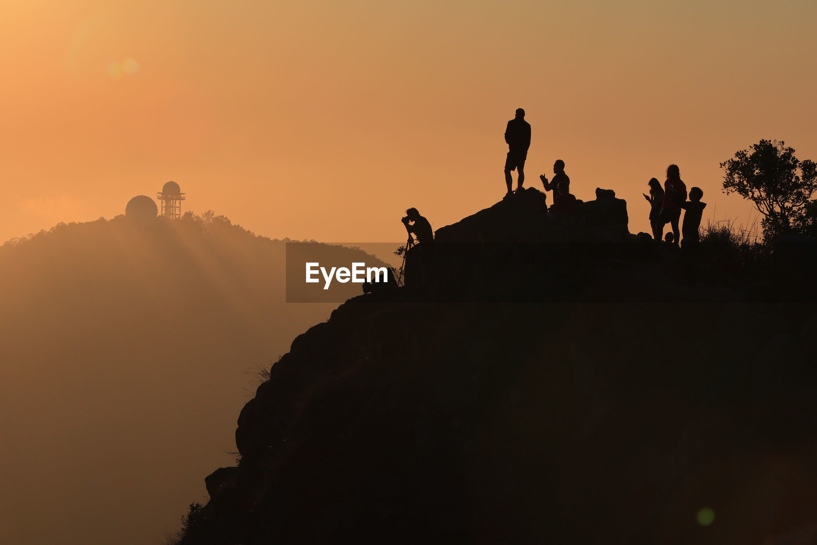 Silhouette man on mountain during sunset