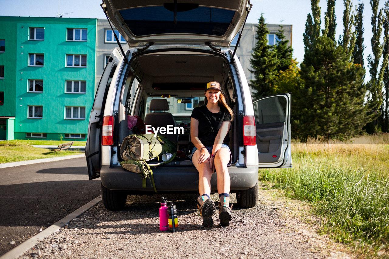 Woman sitting in car trunk
