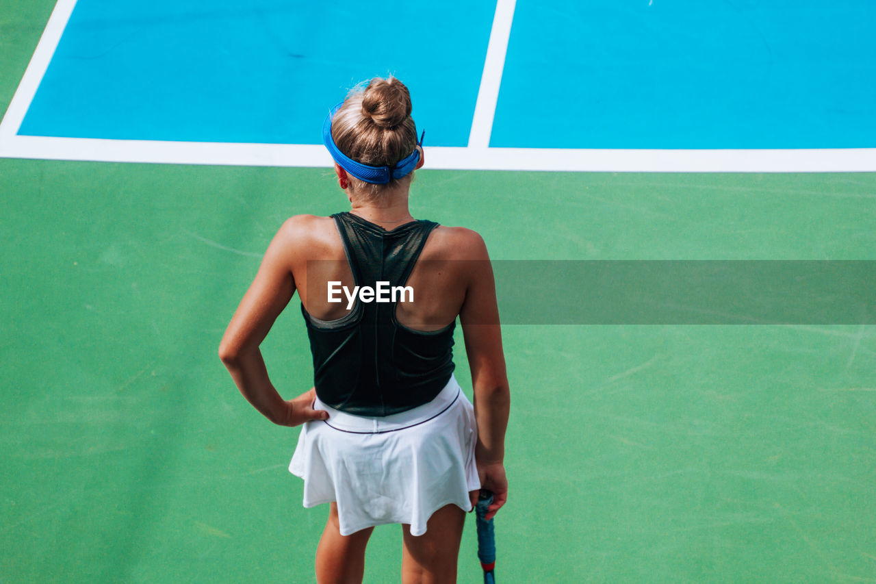 Rear view of girl standing on tennis court