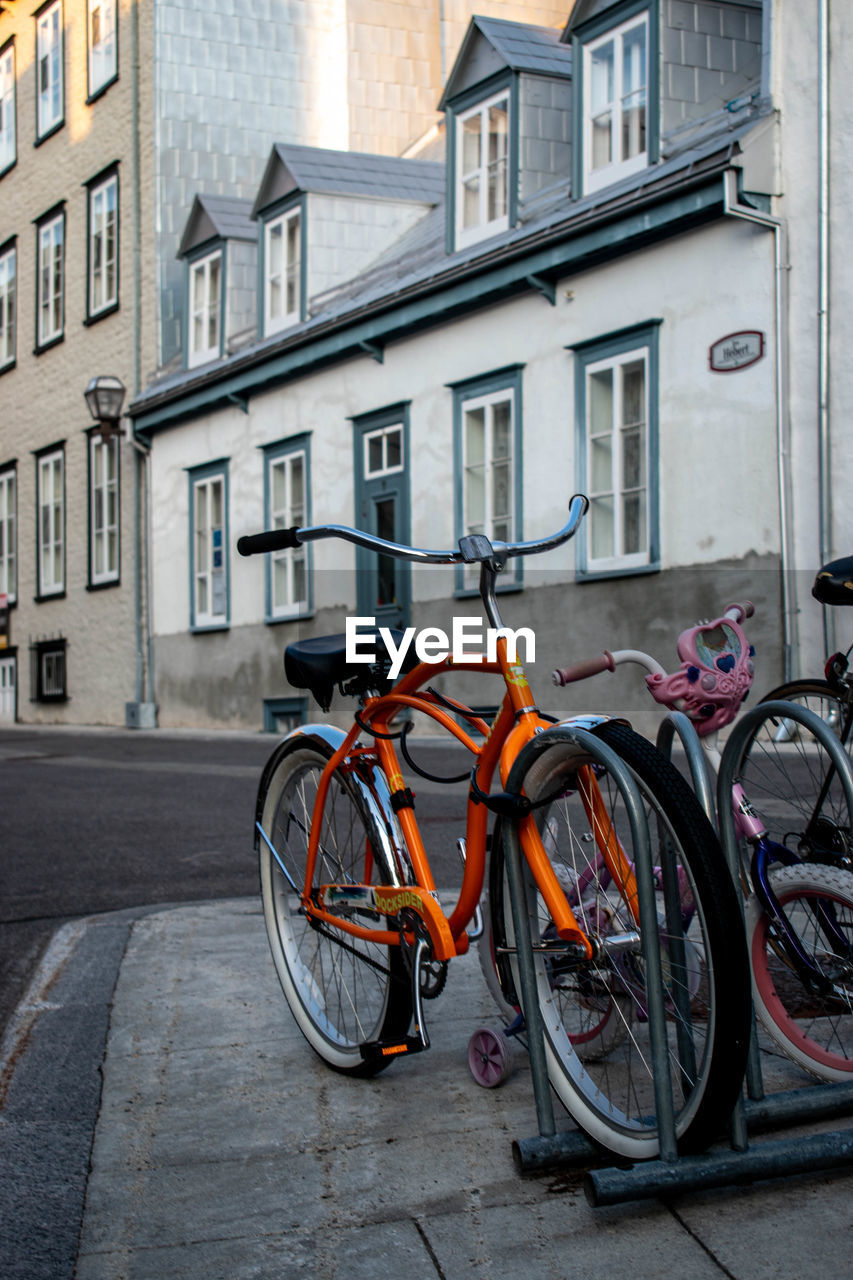 BICYCLE PARKED ON STREET BY BUILDING