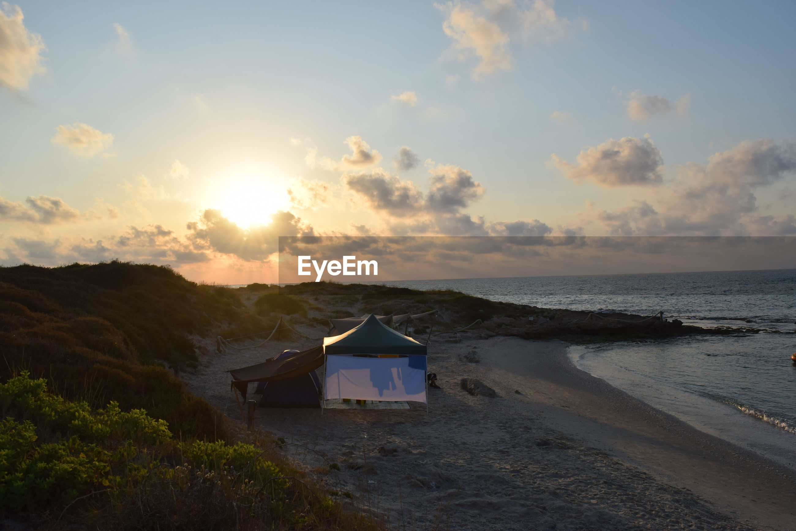 Scenic view tent on beach at sunset