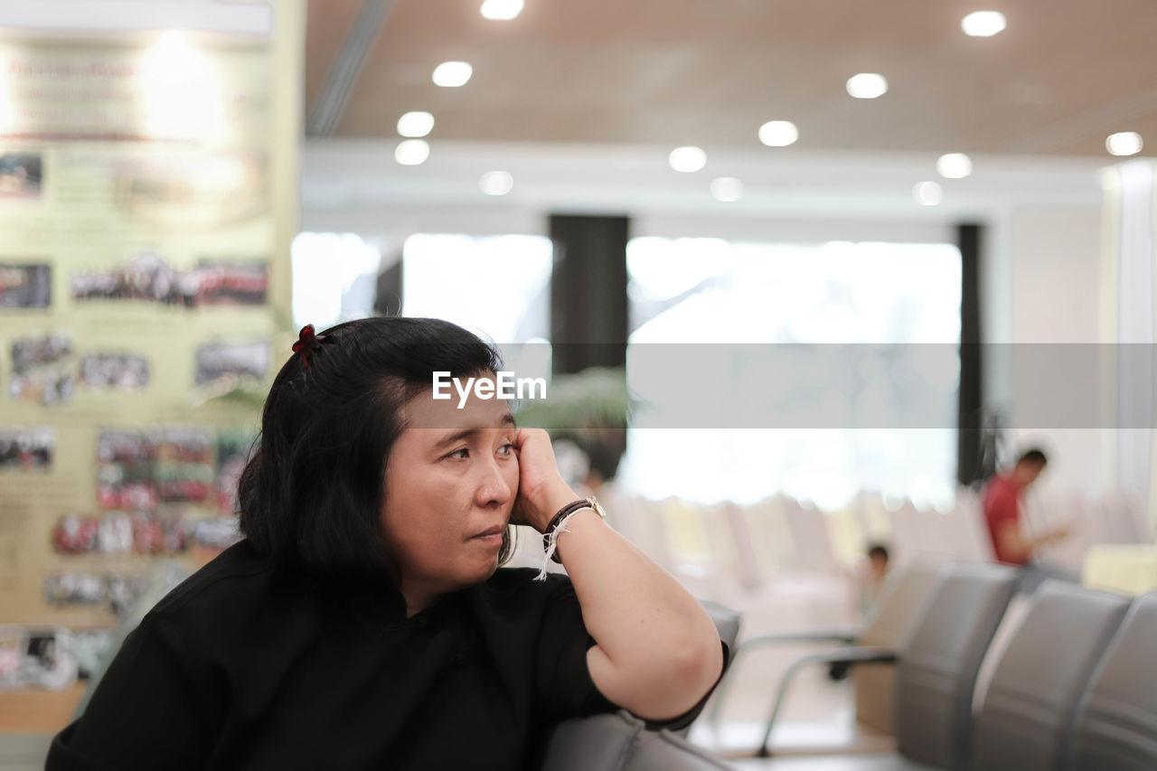 Woman looking away sitting in waiting room