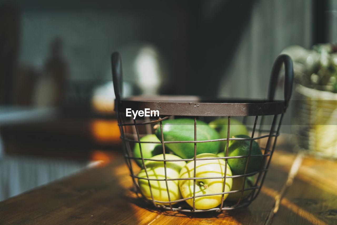 Ripe raw fresh green avocado and apples in metal basket in kitchen hard sun light