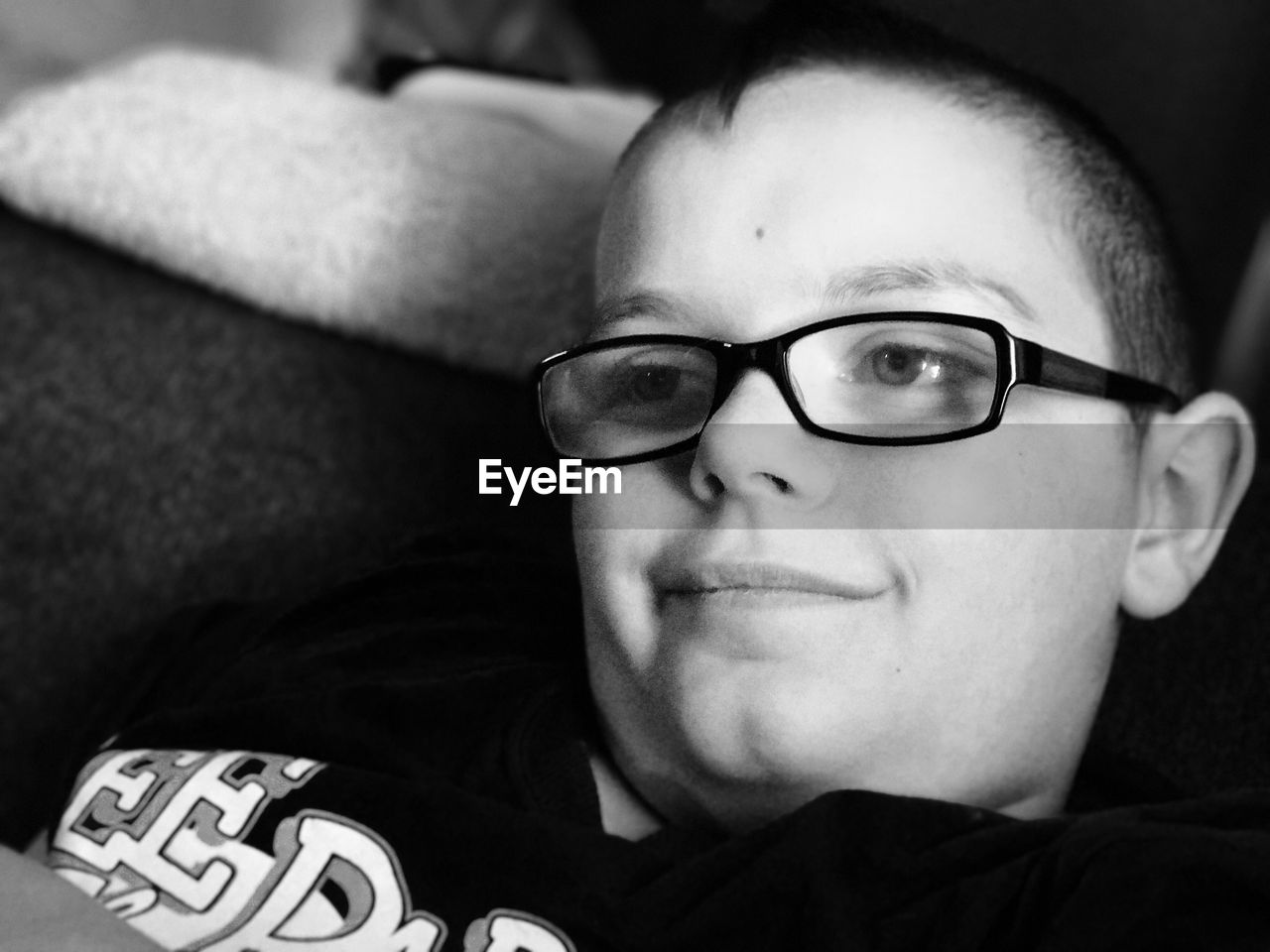 High angle view of boy in eyeglasses looking away at home