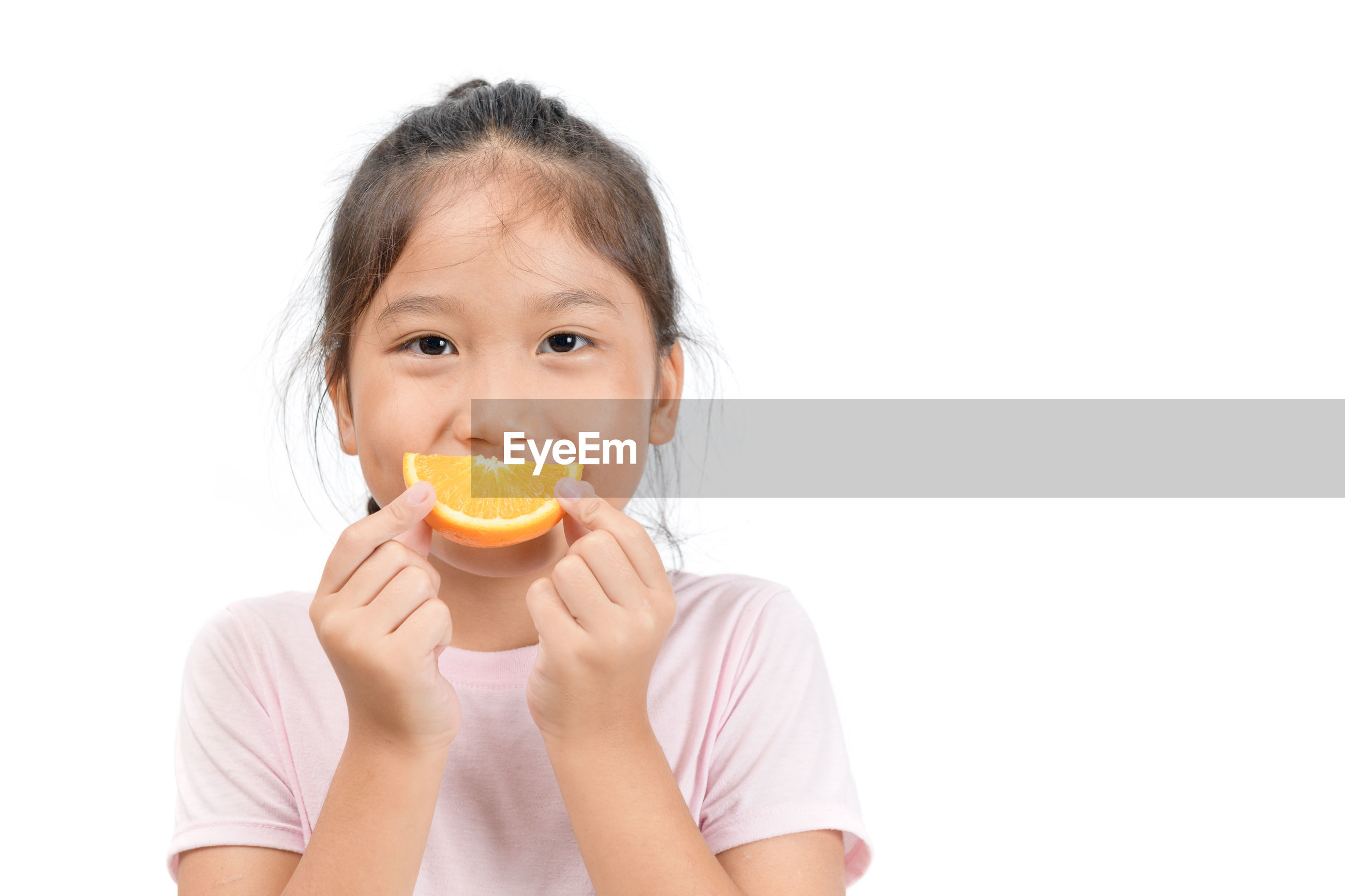 Portrait of holding orange slice standing against white background