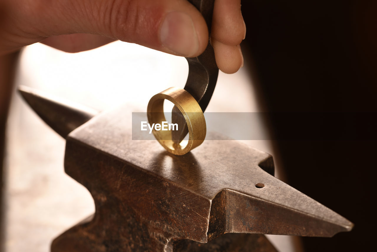 Cropped Hand Of Manual Worker Hitting Metallic Ring In Factory