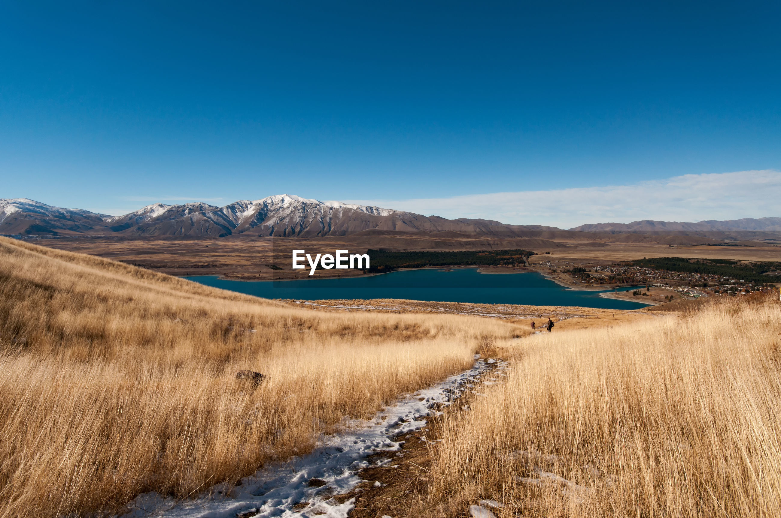 Scenic view of lake amidst landscape against blue sky during sunny day