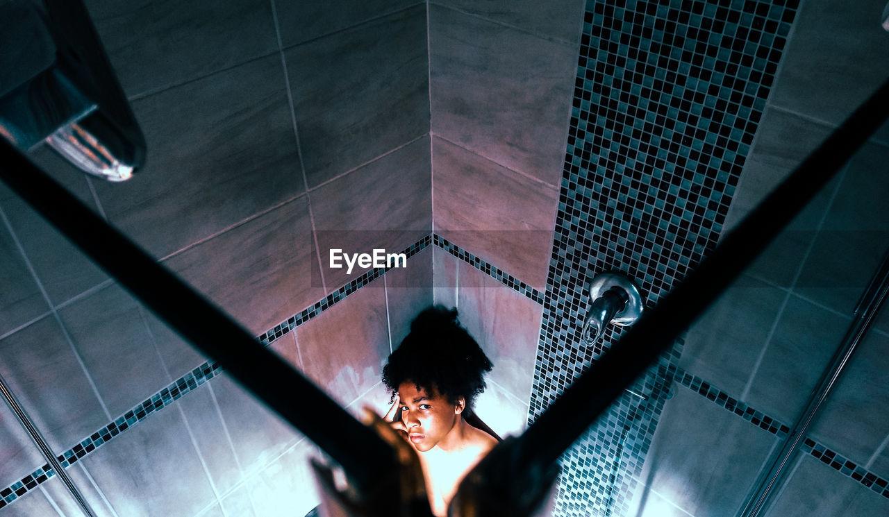 High angle view of teenage boy in bathroom