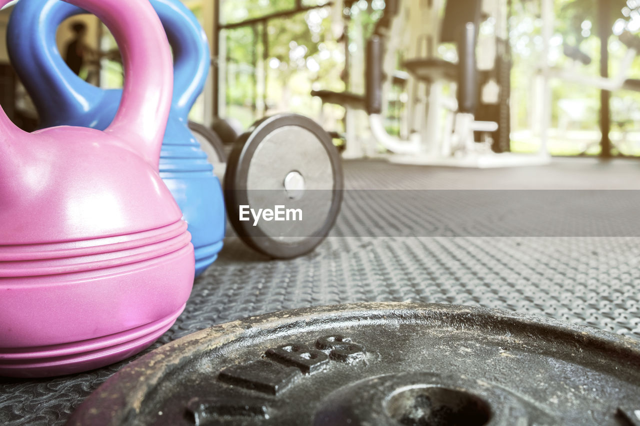 Close-Up Of Dumbbell Plates And Kettlebells In Gym