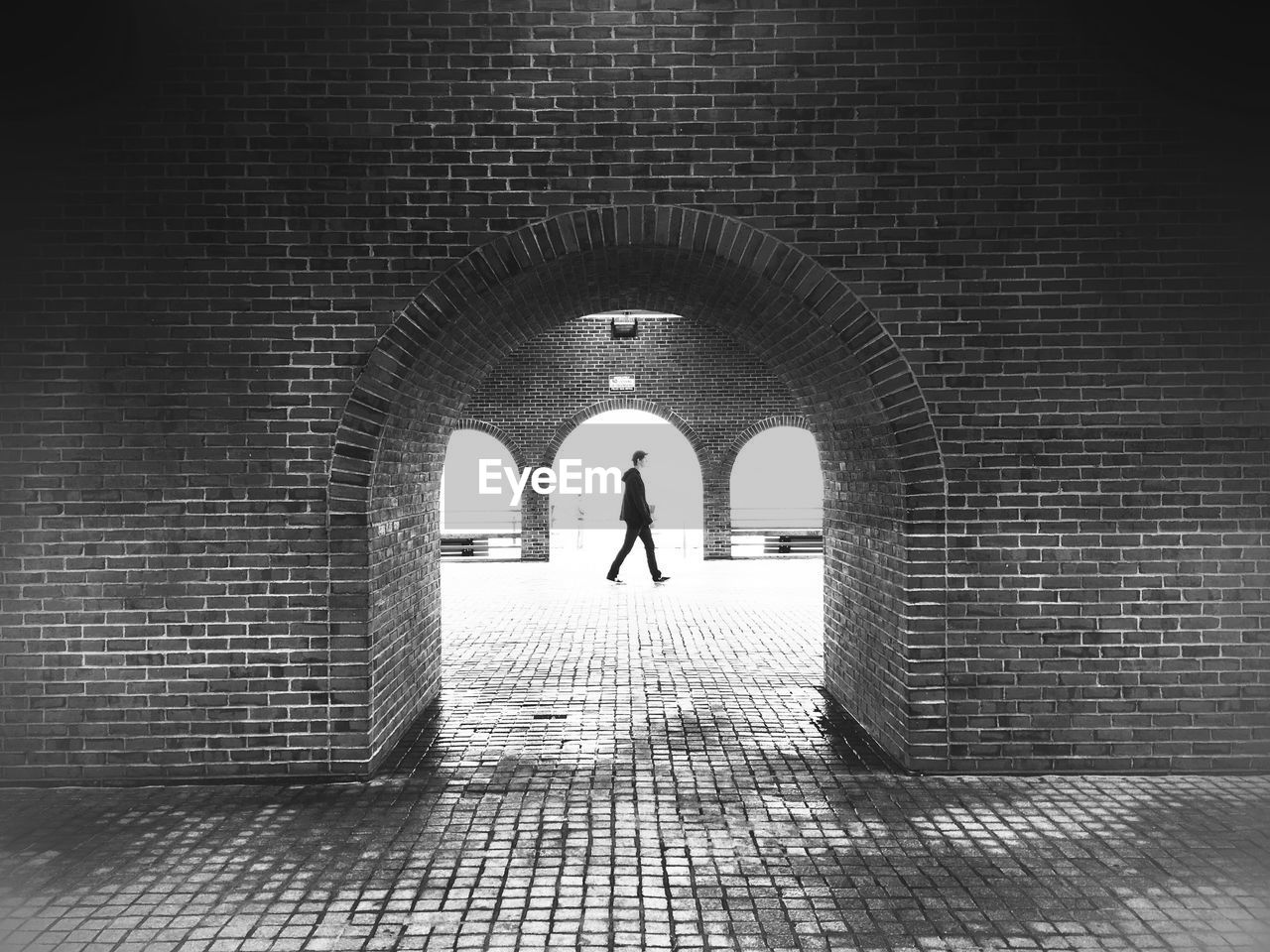 Man walking on footpath seen from archway