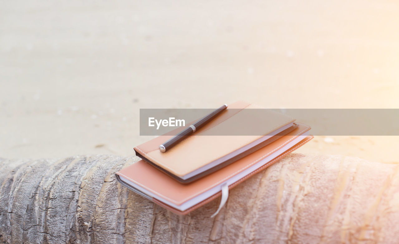 book, publication, still life, no people, close-up, table, communication, wood - material, focus on foreground, indoors, technology, education, pen, sand, literature, land, selective focus, note pad, stack, hardcover book