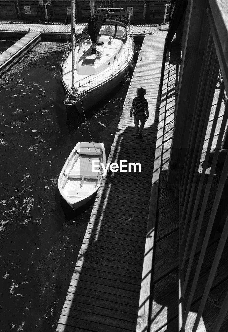 Man walking on pier by boats moored at harbor during sunny day