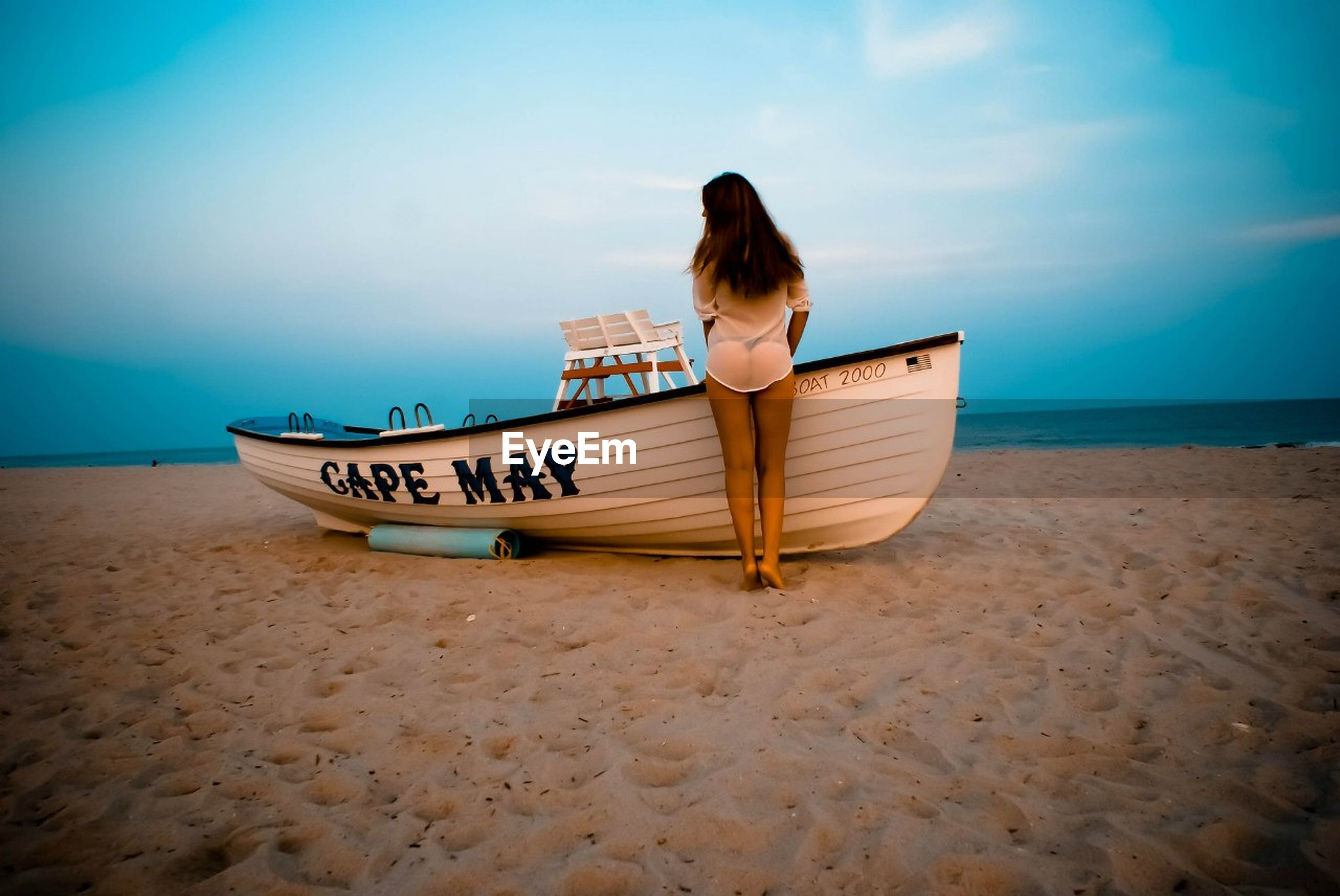 Rear view of sensuous woman standing by boat at beach against sky