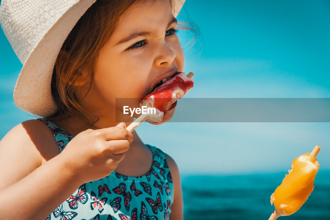 childhood, child, water, food and drink, sea, real people, leisure activity, one person, food, lifestyles, eating, girls, headshot, women, nature, sky, holding, beach, innocence, horizon over water, outdoors, temptation