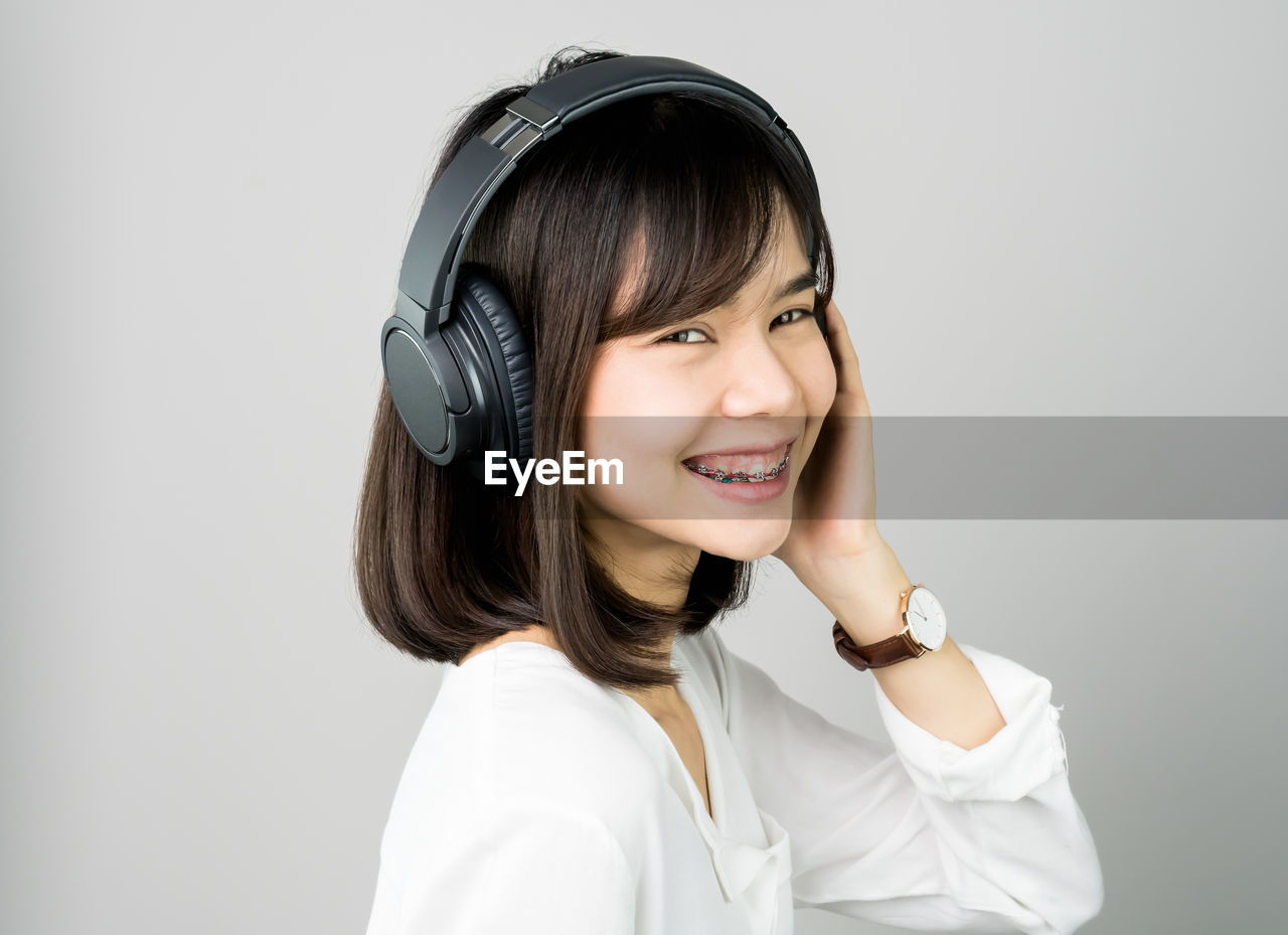 Portrait Of Cheerful Young Woman Listening Music On Headphones Against White Background