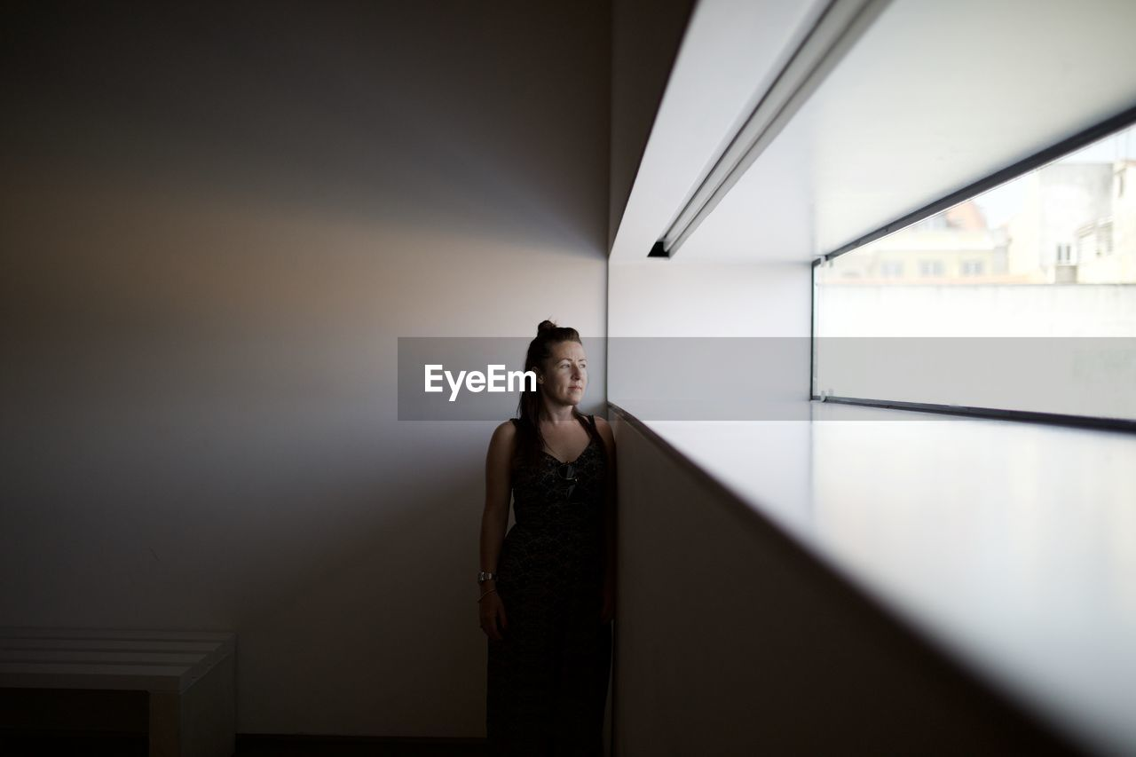 Thoughtful Woman Looking Through Window While Standing Against Wall At Home