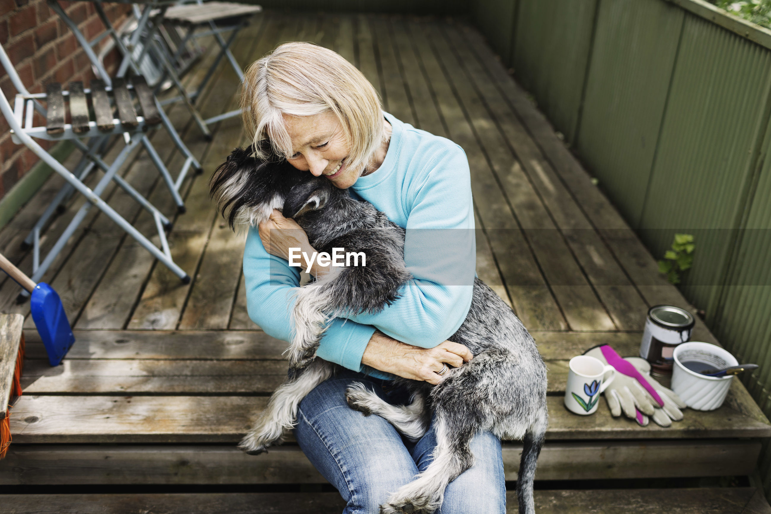 MIDSECTION OF WOMAN HOLDING DOG SITTING OUTDOORS